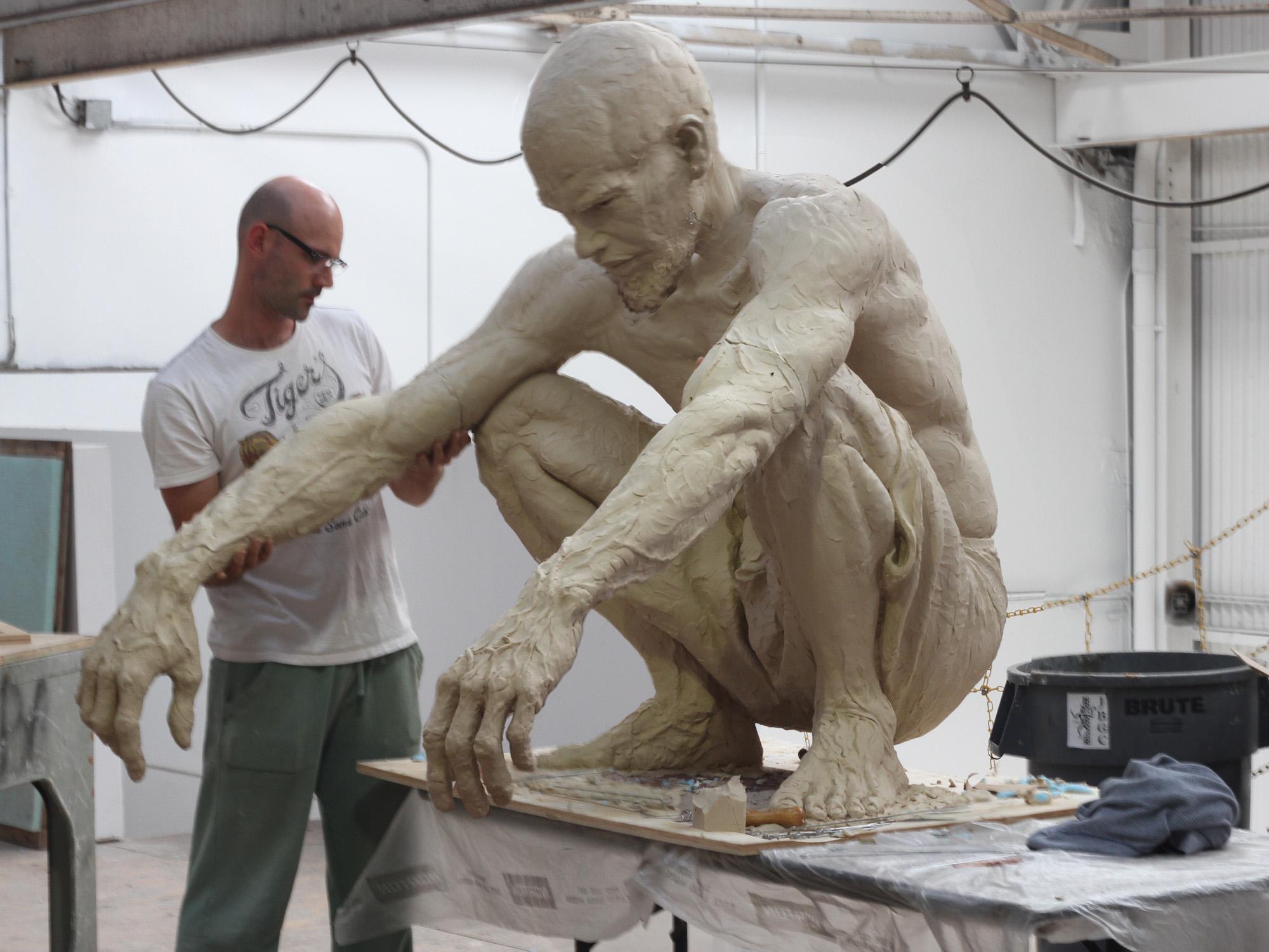 A man making a sculpture of another man